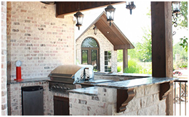 Custom outdoor kitchen built by CCH Pools in Longview Texas featuring a stainless steel grill, brick work and bar top.