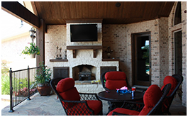 Custom outdoor living space built by CCH Pools a custom pool builder in Longview, Texas. Red chairs around a table against a white brick fireplace with an outdoor TV above