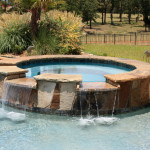 round stone work spa with dual overflow channels into pool