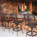 bar top of outdoor kitchen with wrought iron bar stools