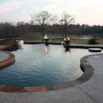 pool with fire accents and in water blue tiled table top