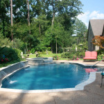 curved and rectangular pool with spa and water spouts