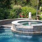 white marble rounded spa with overflow waterfall