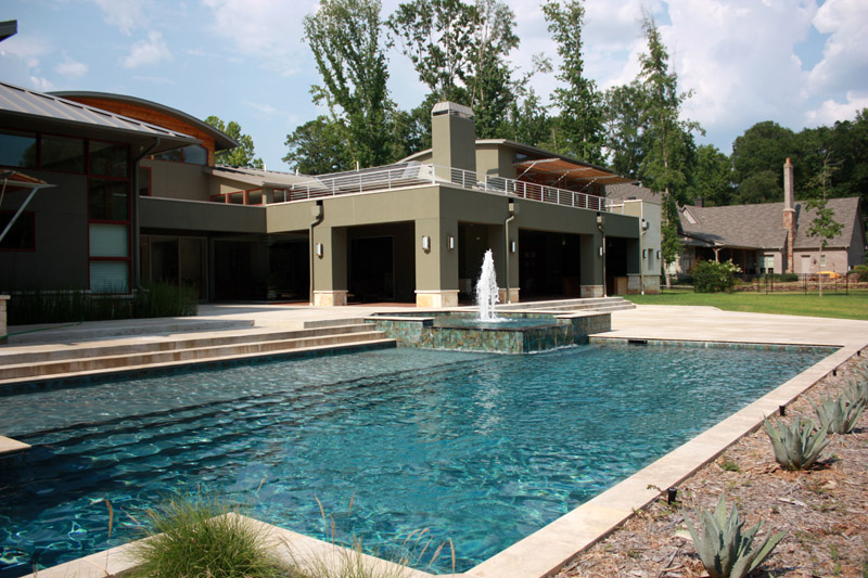 rectangular pool with water fountain shooting out of hot tub