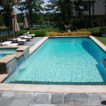 better view of rectangular pool with square spa and seating area with chaise lounge chairs with white cushions