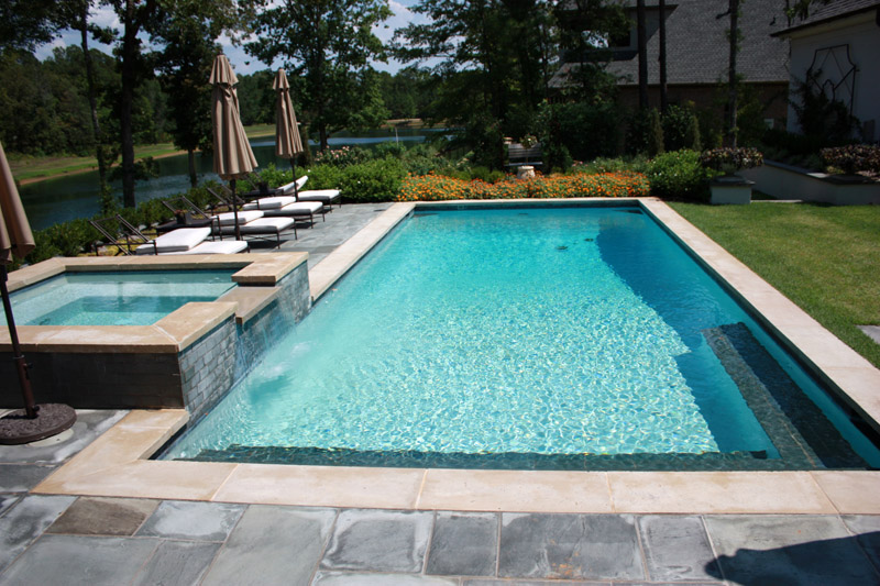 better view of rectangular pool with square spa and seating area with chaise lounge chairs with