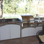 stainless steel outdoor kitchen with white rounded cabinet doors
