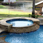 round spa with stepped waterfall into pool