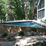 small triangular pool with large retaining wall