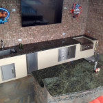 outdoor kitchen bar with TV, neon beer signs and stainless steel appliances