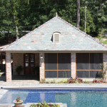 4 brick column pool house with pitched roof and patio