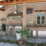 outdoor kitchen with vent hood and stainless steel appliances against chicago style brick