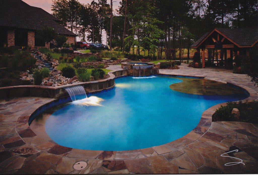 Pool designed and built by CCH Pools in Longview Texas, beautiful stone work with a torquoise blue pool liner, water features and hot tub