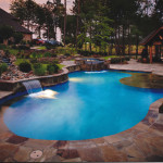 curved edge pool with flat water spouts, lighting and stone work