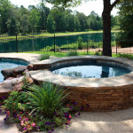 stone round hot tub with rock feature