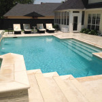 White stone pool with light blue liner and seating area
