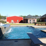 rectangular pool with spa, diving board and 3 water fountains