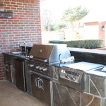 decoratively tiled outdoor kitchen with stainless steel appliances against red brick home