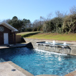 small rectangular pool with spa and water fountains