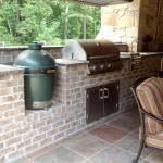 brick outdoor kitchen with green egg smoker and stainless steel grille