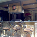 outdoor kitchen with sun clock and wrought iron bar stools